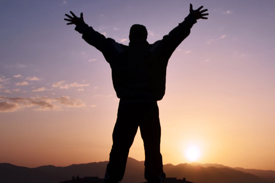 Man on top of mountain saluting sun
